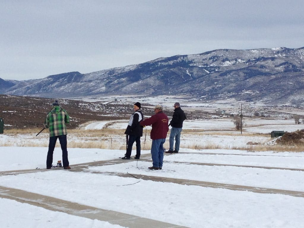 a group preparing to shoot 12-gauge shot guns at the shooting range with a layer of snow on the ground