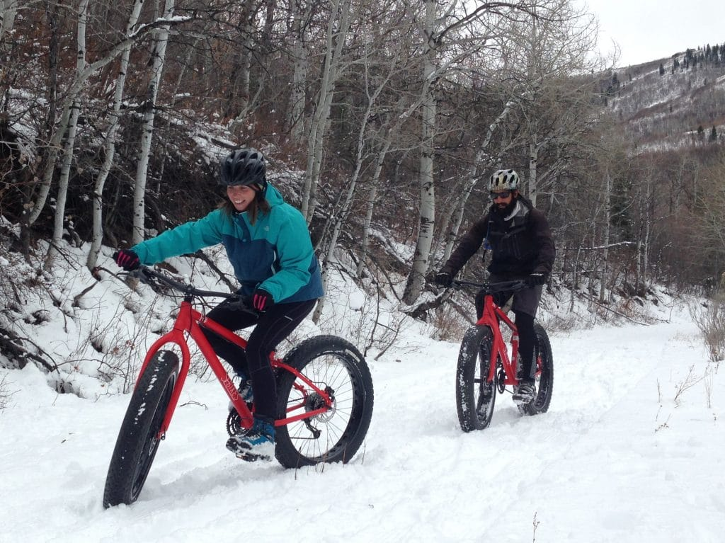 two people riding bikes with wide tires through snow-covered trails