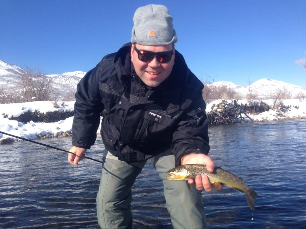 Proud man holding brown trout during while winter fishing