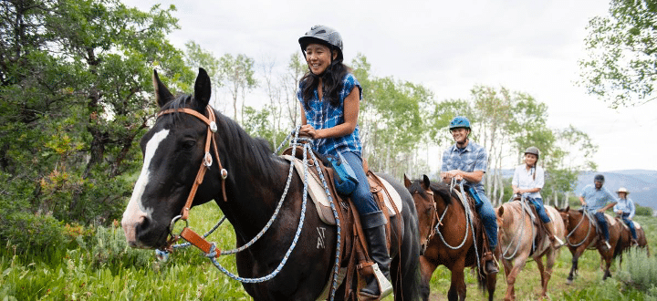 Family riding horses in a nose-to-tail ride