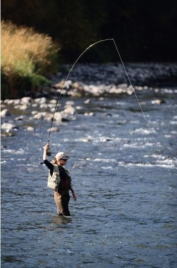 woman fly fishing in the middle of a river