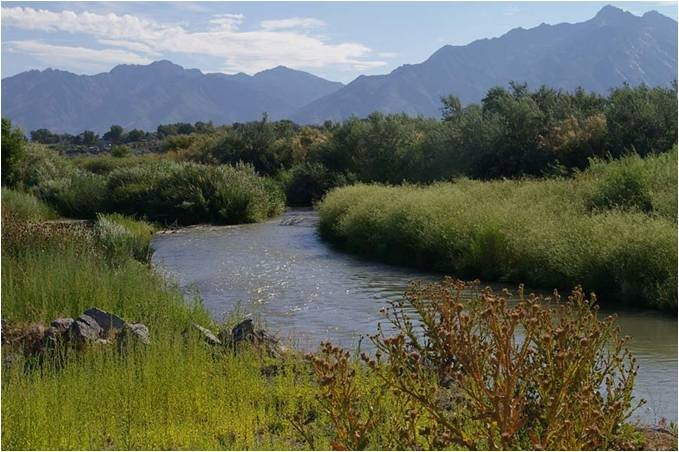 slow moving Jordan river with mountain peaks in the background