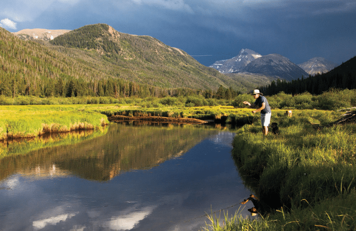 Person fishing the Uinta River with mountains in the background