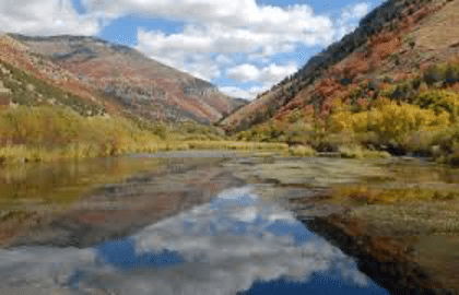 Logan river in fall. Nearby mountains have changing colors and clouds in the sky