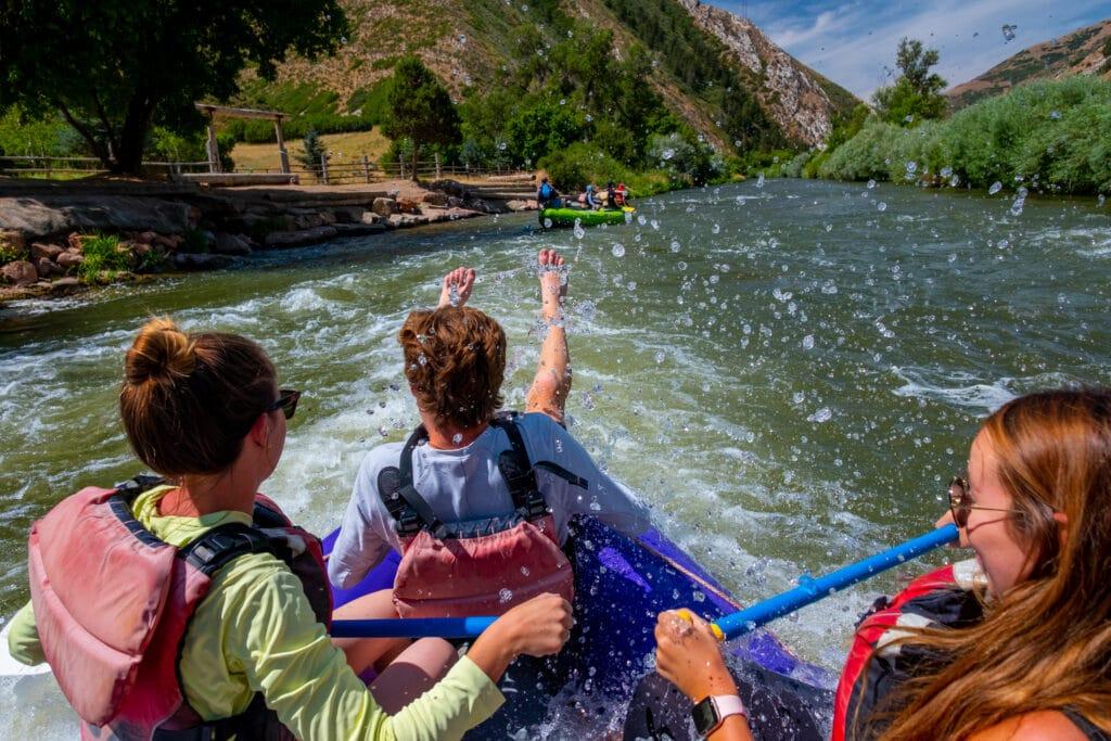 white water rafting in park city utah.  big splash and happy people on board the raft